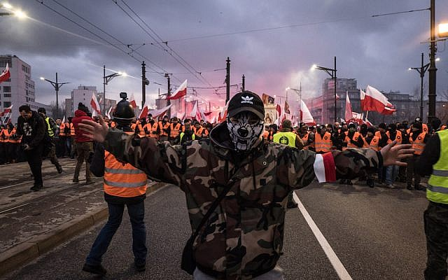 A Man With His Face Covered As Thousands Gather For The Annual Nationalist March Of Poland