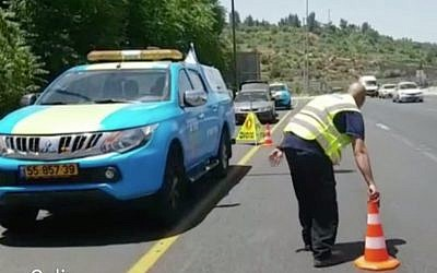A driver of one of Netivei Israel's new mobile units places a traffic cone on a highway in Israel. (Screen capture: Channel 2)