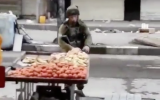 An Israeli soldier apparently steals fruit from a Palestinian vendor during a violent demonstration in the West Bank city of Hebron on December 10, 2017. (Screen capture)