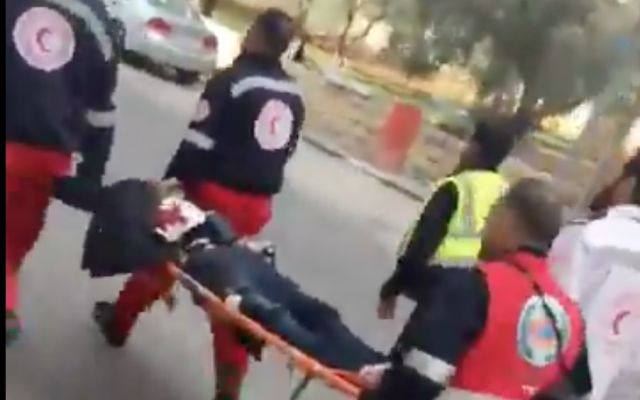 A Palestinian assailant wearing what appears to be a suicide bomb belt is carried away by Red Crescent medics after he stabbed a border guard and was shot in Ramallah on December 15, 2017. (Screen capture)