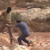 An Israeli settler assaults rabbi-activist Arik Ascherman who was accompanying a group of Palestinian farmers to their fields near Nablus on October 23, 2015. (Screen capture/ YouTube)