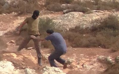 An Israeli settler assaults rabbi-activist Arik Ascherman who was accompanying a group of Palestinian farmers to their fields near Nablus on October 23, 2015. (Screen capture/ YouTube)