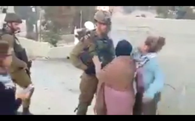 A Palestinian girl slaps an IDF officer in the face in an apparent attempt to get him to respond violently so the encounter could be filmed and shared online, during a protest in the West Bank village of Nabi Saleh on December 15, 2017. (Screen capture)