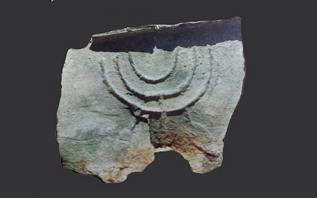 A copper basin fragment with the Menorah symbol was found next to Kibbutz Beit Zera, together with another fragment that bears an inscription in Arabic. Umayyad period (early 8th century). (A. Peled)
