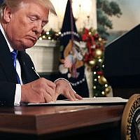 US President Donald Trump signing a proclamation that the US government will formally recognize Jerusalem as the capital of Israel, at the White House in Washington, DC, December 6, 2017. (Chip Somodevilla/Getty Images via JTA)