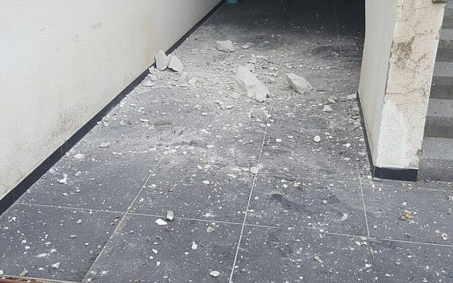 The damage cause by a mortar shell fired from the Gaza Strip that landed at the entrance to a building in the Shaar Hanegev region, December 29, 2017. (Israel Police)