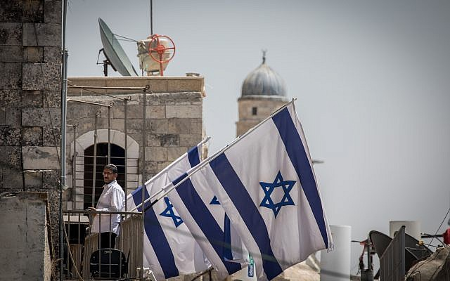 A Jewish man stand on the balcony of Ateret Cohanim yeshiva in Jerusalem's Old City, on August 1, 2017. (Nati Shohat/Flash90)