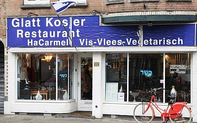 A man waving a Palestinian flag smashed the windows of the HaCarmel kosher restaurant in Amsterdam, December 7, 2017. (Ginopress B.V./AFP/Getty Images/via JTA)