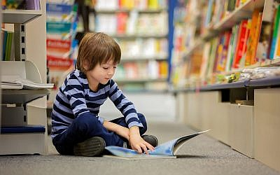Illustrative image of a boy, sitting in a book store, reading (tatyana_tomsickova/ IStock by Getty Images)