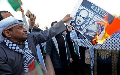 A Kuwaiti demonstrator burns a poster of Israeli Prime Minister Benjamin Netanyahu during a demonstration in front of the National Assembly in Kuwait City on December 9, 2017, against US President Donald Trump's recongition of Jerusalem as the capital of Israel. (AFP/Yasser Al-Zayyat)