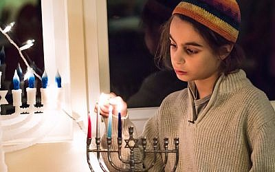 Lahav Zaken lights the Hanukkah menorah (Hillary Zaken)