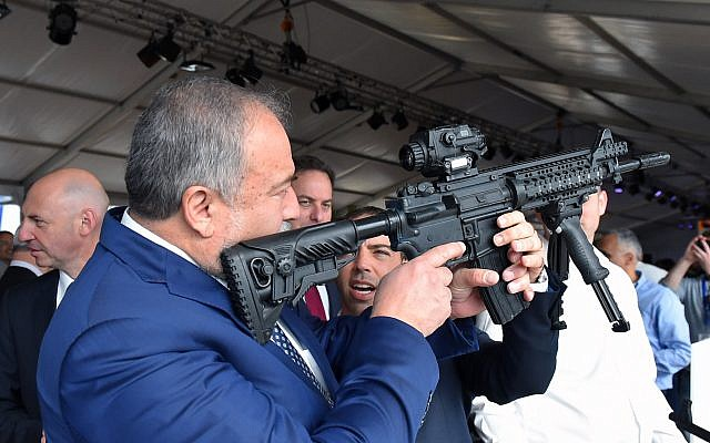 Defense Minister Avigdor Liberman inspects a sight on a rifle at a weapons manufacturing plant in the southern Israeli town of Sderot on December 14, 2017. (Ariel Hermoni/Defense Ministry)