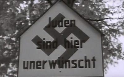 """A sign reading """"Jews are not wanted here,"""" erected somewhere in Germany following the introduction by the Nazis of the Nuremberg race laws in 1935. (Youtube screenshot)"""