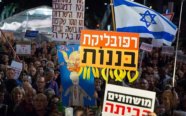 Israelis holding signs and shout slogans during a protest against the corruption of the government in Tel Aviv on December 16, 2017. (Miriam Alster/Flash90)