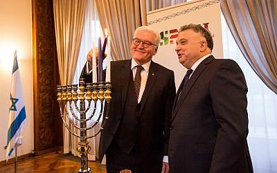 German President Frank-Walter Steinmeier (left) lights a menorah at Israel's Embassy in Berlin on December 15, 2017, alongside Israel's Ambassador to Germany Jeremy Issacharoff (Courtesy Israeli Embassy, via Facebook)