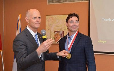 Florida Governor Rick Scott (left) gives an award to Jack Ross, VP North America for StemRad, for the Israeli startup's contribution to the Florida tech scene (Yosi Zliger)