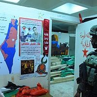 An IDF soldier stands next to what the army referred to as 'incitement materials' that were seized in overnight raids on December 14, 2017. (Courtesy: IDF)