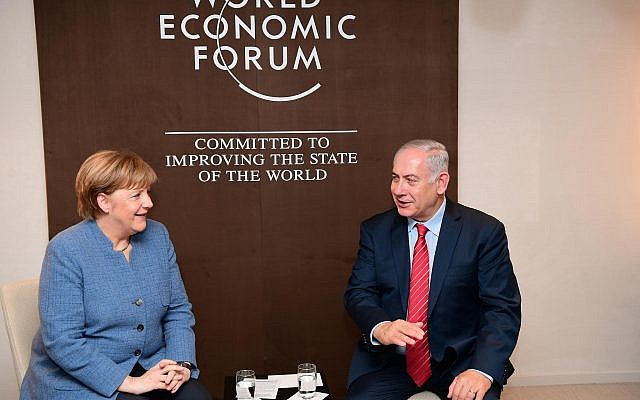 Prime Minister Benjamin Netanyahu meets with German Chancellor Angela Merkel, in Davos, Switzerland, on January 24, 2018. (Amos Ben Gershon/ GPO)
