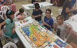 Kids play 'Jewish Luck,' the first Russian-language Jewish board game, created by Konstantin Zinkoff. (Courtesy)