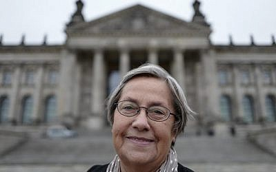 Karin Felix, who served as a guide at the Reichstag parliament building for a quarter-century, poses in front the Reichstag building in Berlin on November 23, 2017. (AFP/John MacDougall)