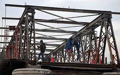 A picture taken on December 19, 2017 shows a construction worker welding on the Old Metal bridge, the first bridge Of Mosul, as part of a repair contract. (AFP PHOTO / Ahmad MUWAFAQ)