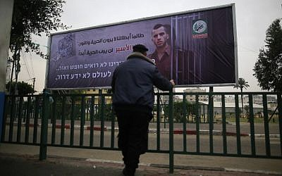 A Palestinian Hamas police officer looks at a billboard bearing a portrait of slain Israeli soldier Oron Shaul in Gaza City on December 29, 2017. The writing in Arabic reads: ''As long as our heroes don't see freedom and light: This captive will never see freedom'' (AFP PHOTO / MOHAMMED ABED)