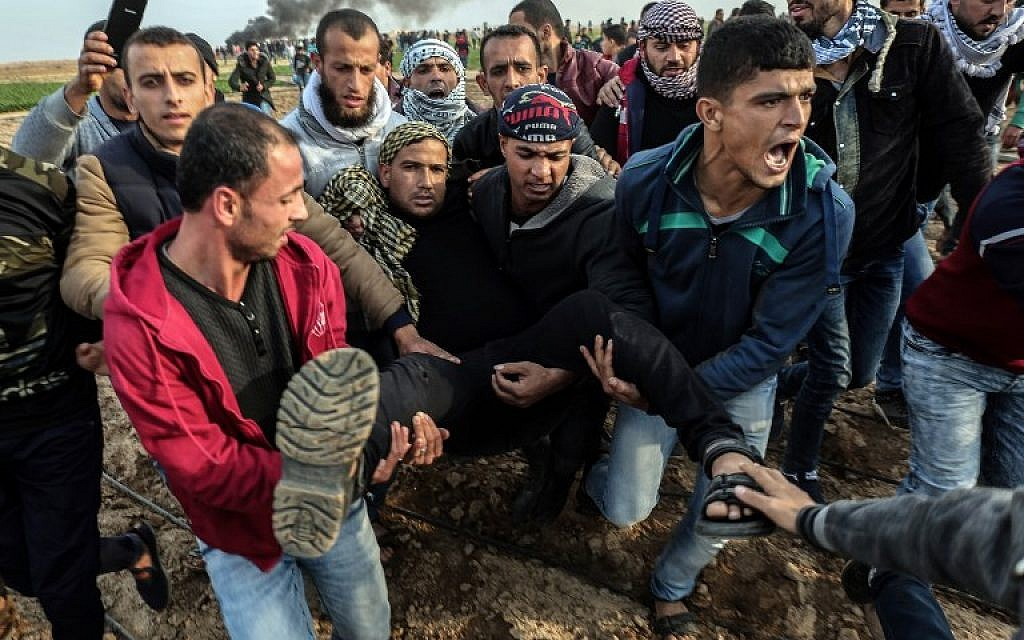 Palestinian protesters carry a wounded man during clash with Israeli forces near the Israel-Gaza border east of the southern Gaza strip city of Khan Yunis on December 29, 2017. (AFP PHOTO / SAID KHATIB)