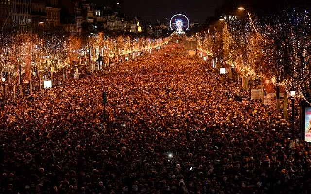 New Year revellers gather on the Champs-Elysees avenue in Paris on December 31, 2017. (AFP PHOTO / GUILLAUME SOUVANT)