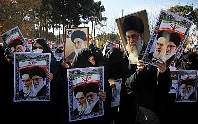 Pro-government demonstrators hold posters of Iran's supreme leader, Ayatollah Ali Khamenei (L) and Iran's founder of Islamic Republic, Ayatollah Ruhollah Khomeini during a march in Iran's holy city of Qom on January 3, 2018. (AFP PHOTO / Mohammad ALI MARIZAD)