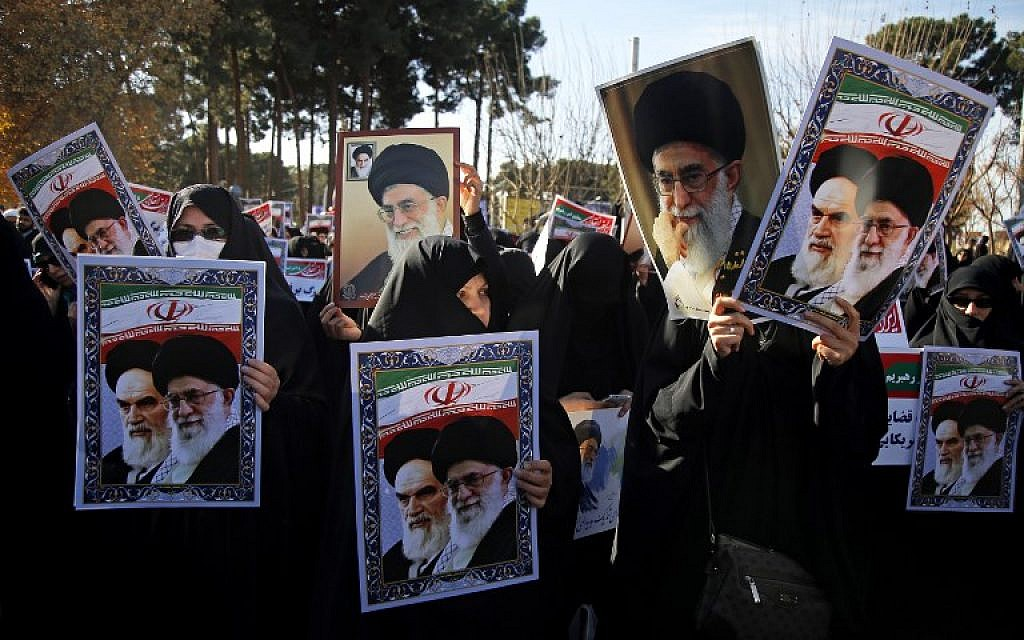 Pro-government demonstrators hold posters of Iran's supreme leader, Ayatollah Ali Khamenei, left, and Iran's founder of Islamic Republic, Ayatollah Ruhollah Khomeini during a march in Iran's holy city of Qom, 130 kilometres south of Tehran, January 3, 2018. (Mohammad ALI MARIZAD/AFP)