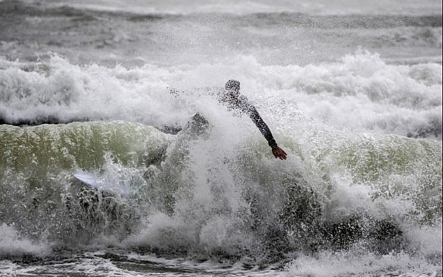 An man surfs in the Israeli coastal city of Netanya on January 5, 2018 as a storm hits the country. / AFP PHOTO / JACK GUEZ