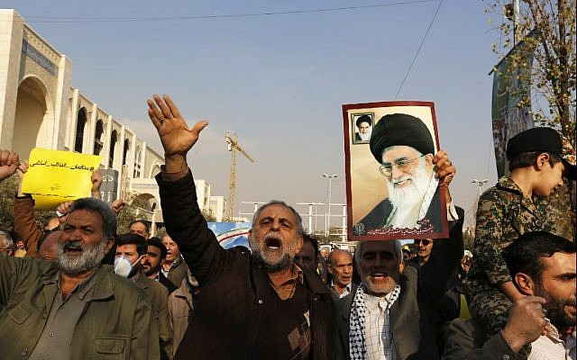 Pro-government demonstrators hold a poster of Iran's Supreme Leader, Ayatollah Ali Khamenei (R) and shout slogans of support during a march after the weekly Muslim Friday prayers in Tehran on January 5, 2018. (AFP Photo/Atta Kenare)