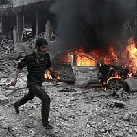 A Syrian man runs past a burning vehicle following reported bombardment by Syrian and Russian forces in the rebel-held town of Hamouria, in the Eastern Ghouta, on January 6, 2018. (AFP/ABDULMONAM EASSA)