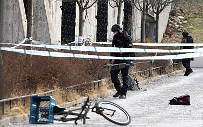 A policeman investigates a cordoned off area outside Varby Gard metro station south of Stockholm where one person died and one was injured in an explosion on January 7, 2018. (AFP PHOTO / TT News Agency / Henrik MONTGOMERY)