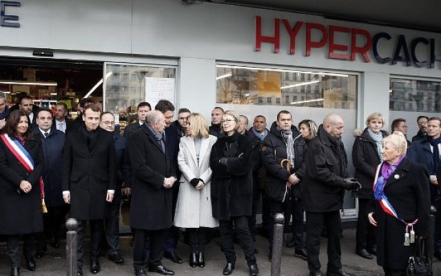 Paris mayor Anne Hidalgo (1st L), French President Emmanuel Macron (2nd L), and others pay their respect during a memorial ceremony outside the Hyper Cacher supermarket to pay a tribute to the shoppers at the kosher store who were killed three years ago by an Islamist gunman in Paris, January 7, 2018. (AFP PHOTO / POOL / CHRISTIAN HARTMANN)