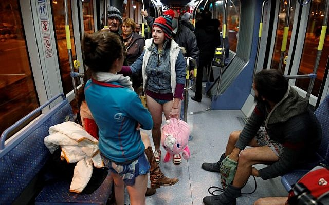 "People taking part in the annual international ""No Pants Subway Ride"" day travel on the Jerusalem light train on January 7, 2018. (AFP PHOTO / AHMAD GHARABLI)"