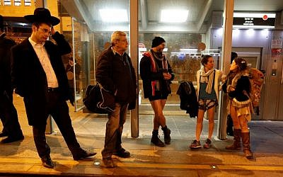 """People taking part in the annual international """"No Pants Subway Ride"""" day wait for the Jerusalem light train on January 7, 2018. (AFP PHOTO / AHMAD GHARABLI)"""