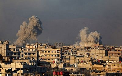 Smoke rises from buildings following air strikes on the rebel-held besieged town of Arbin, in the eastern Ghouta region on the outskirts of the capital Damascus on January 8, 2018.  (AFP / Amer ALMOHIBANY)
