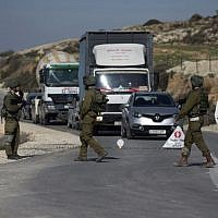 Illustrative. Israeli soldiers inspect cars at a checkpoint near the West Bank city of Nablus on January 10, 2018. (Jaafar/Ashtiyeh/AFP)