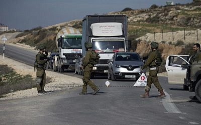 Illustrative: Israeli soldiers inspect cars at a checkpoint near the West Bank city of Nablus on January 10, 2018. (Jaafar/Ashtiyeh/AFP)