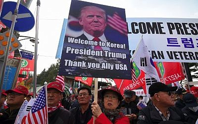 A file photo taken on November 8, 2017 shows pro-Trump supporters holding a placard with a picture of US President Donald Trump as they wait for Trump outside the National Cemetery in Seoul. (AFP Photo/Jung Yeon-je)