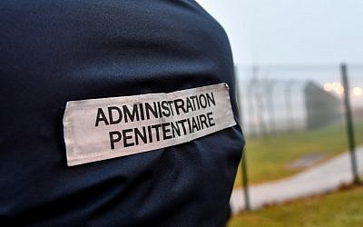 The penitentiaty administration tag is pictured on a warden's jacket as prison wardens gather outside the high-security prison of Vendin-le-Vieil, northern France, on January 12, 2018, a day after three prison guards have been injured in a blade attack by a German Al-Qaeda terrorist. (AFP PHOTO / Denis Charlet)