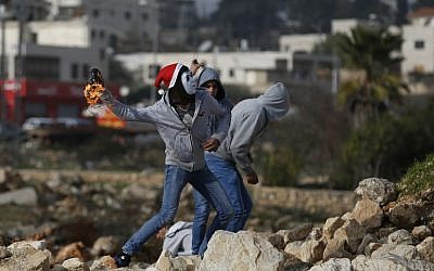 Illustrative. Palestinians protesters throw a firebomb towards Israeli security forces during clashes on January 12, 2018 north of Ramallah in the Israeli-occupied West Bank.  (AFP PHOTO / ABBAS MOMANI)