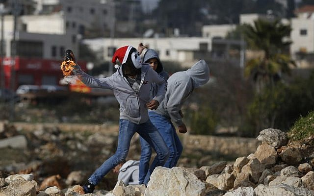 Illustrative. Palestinians protesters throw a firebomb towards Israeli security forces during clashes on January 12, 2018 north of Ramallah in the West Bank.  (AFP PHOTO / ABBAS MOMANI)