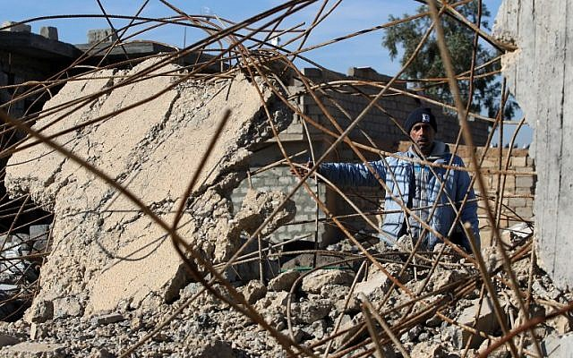 An Iraqi man, from the Shabak community, stands amidst the rubble of a house which was destroyed by Islamic State (IS) group jihadists in the village of Baz Gerkan east of Mosul on January 10, 2018. (AFP Photo/Ahman Al-Rubaye)