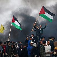 Illustrative: Palestinian protesters wave national flags during clashes with Israeli security forces on the eastern outskirts of Gaza City, near the border with Israel, on January 12, 2018. (AFP PHOTO / MOHAMMED ABED)