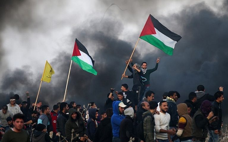 Palestinian protesters wave national flags during clashes with Israeli security forces on the eastern outskirts of Gaza City near the border with Israel