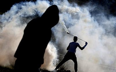 Palestinians clash with Israeli forces at a rally in support of members of the Tamimi family in the West Bank village of Nabi Saleh on January 13, 2018. (AFP/Abbas Momani)