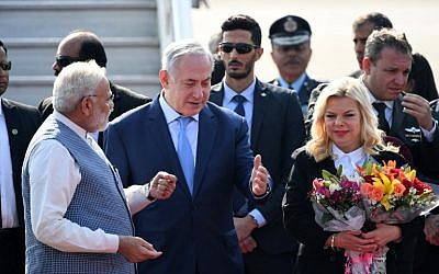 Indian Prime Minister Narendra Modi, left, welcomes Prime Minister Benjamin Netanyahu, center, and his wife Sara Netanyahu on their arrival at the Air Force Station in New Delhi on January 14, 2018. (PRAKASH SINGH/AFP)