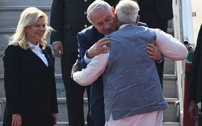 Indian Prime Minister Narendra Modi, right, embraces Prime Minister  Benjamin Netanyahu, as the Israeli leader's wife, Sara, watches on their arrival at the Air Force Station in New Delhi, on January 14, 2018. (PRAKASH SINGH/AFP)
